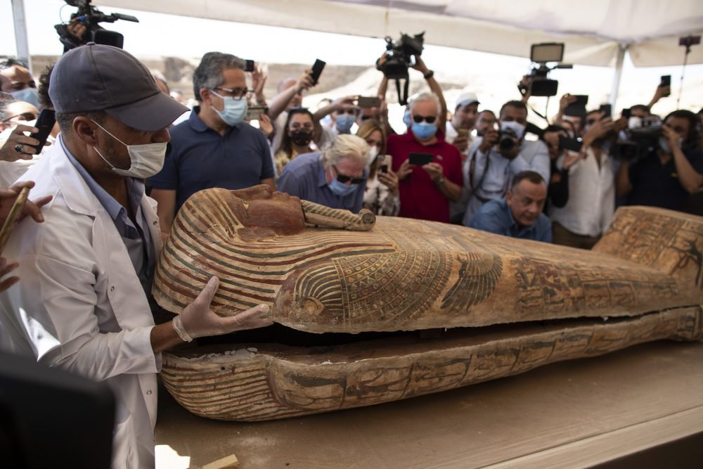 An archeology worker opens a sarcophagus at the Saqqara archaeological site, 30 kilometers (19 miles) south of Cairo, Egypt, on Saturday, Oct. 3, 2020, in the presence of journalists and officials.